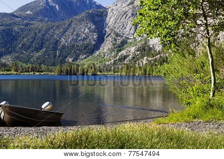 Aluminum Fishing Boat On Shore Of Mountain Lake
