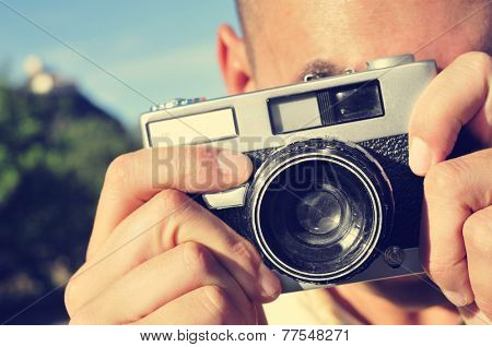 closeup of a young man taking a picture with an old camera outdoors