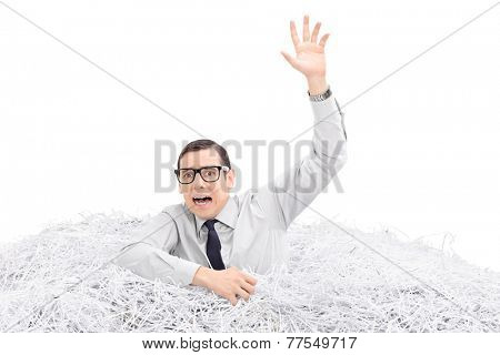 Helpless man drowning in a pile of shredded paper isolated on white background