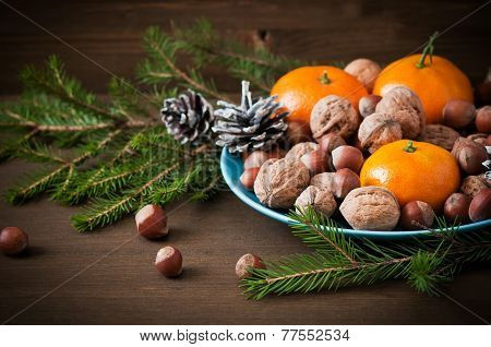 Christmas Concept (decoration). Plate  With Tangerine, Cone And Walnut  On Rustic Wooden Background