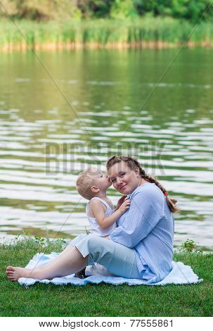 Pregnant woman and her son 2 yo on the green grass