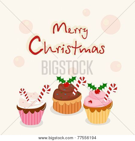 Delicious Cup cakes with mistletoe for Merry Christmas celebration on stylish background.