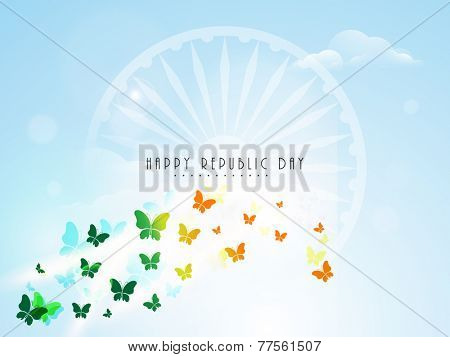 Flying shiny butterflies in saffron and green color with Ashoka Wheel on cloudy blue background for Indian Republic Day celebration.