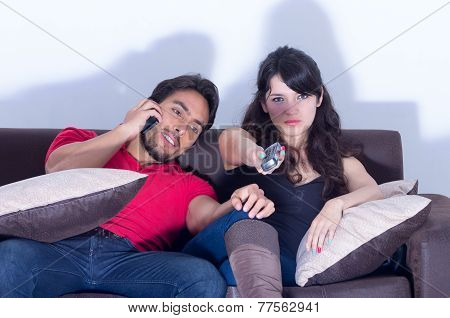 bored girlfriend watching tv while boyfriend chats on the phone