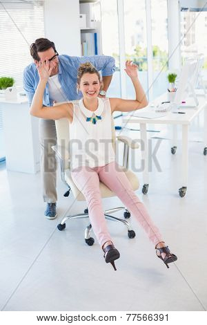 Creative business colleagues having fun on a swivel chair in office