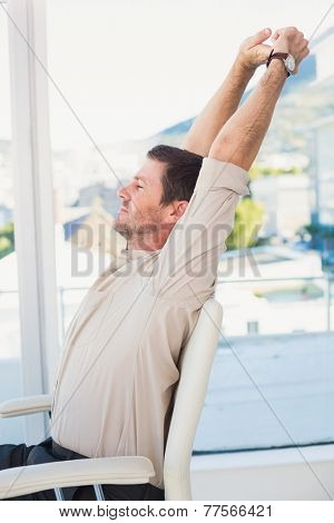 Casual businessman stretching in swivel chair in his office