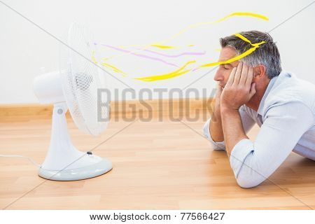 Man lying in front of an electronic fan with ribbons at appartment