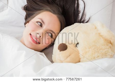 Pretty brunette under the duvet with teddy bear at home in the bedroom