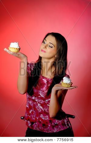 Young Beautiful Girl Eating Two Small Sweet Cake. Red Background. Copy-space