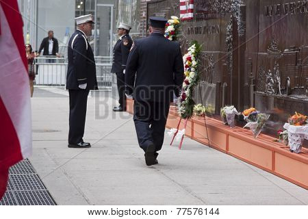 NEW YORK - SEPT 11, 2014: The changing of the guard at the Memorial Wall at FDNY Engine 10 Ladder 10 House on Liberty St . The firehouse is directly across from the WTC site.