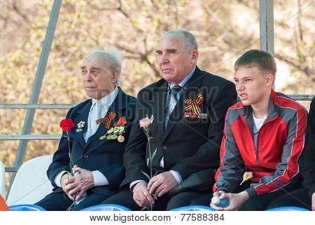 Senior veterans of World War II and boy on tribune