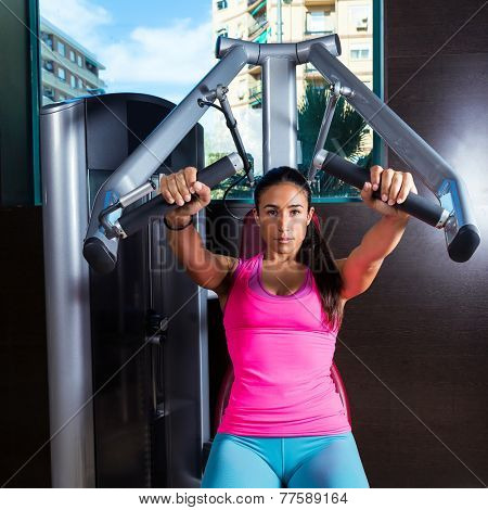 brunette woman seated chest press machine workout exercise at gym