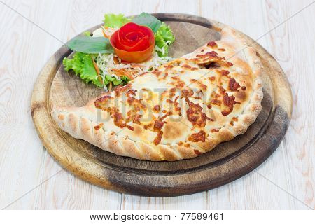 Calzone Pizza On Wooden Dish