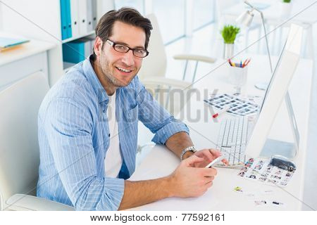 Photo editor typing text message while looking at camera in office