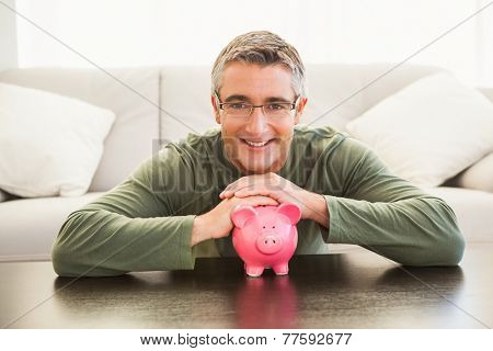 Smiling man with a pink piggy bank at home in the living room