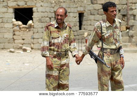 Yemeni military men hold hands at the security checkpoint, Hadramaut valley, Yemen.