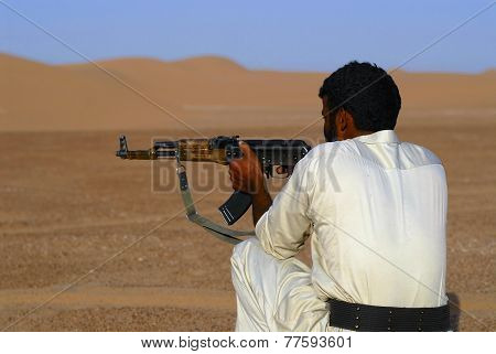 Yemeni man aim with Kalashnikov machine gun in the desert, Hadramaut valley Yemen.