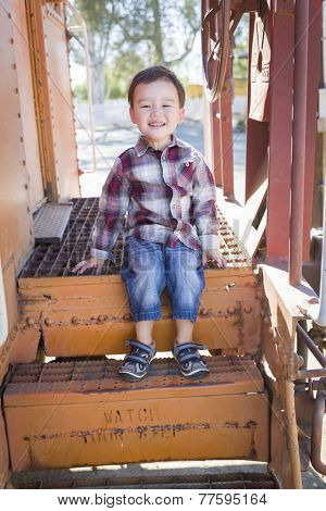 Cute Young Mixed Race Boy Having Fun Outside Sitting on Railroad Car Steps.