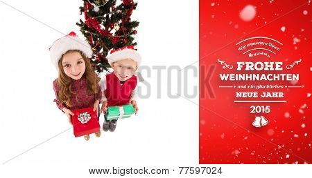 Festive little siblings smiling at camera holding gifts against red vignette