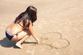 image of drow  - Woman is drowing a heart on the sand - JPG