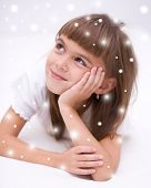 stock photo of daydreaming  - Cute girl is daydreaming lying on the floor over snowy background  - JPG