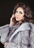 image of mink  - Beautiful brunette woman in mink fur coat isolated on black background - JPG