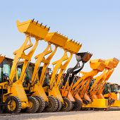 stock photo of construction machine  - Row of heavy construction excavator machine  against blue sky in a construction site - JPG
