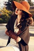 stock photo of coat  - fashion outdoor photo of beautiful ladylike woman with dark hair wearing elegant coat with furfelt hat and leather gloves - JPG