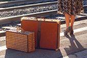 image of carry-on luggage  - Details of woman waiting at the railway station - JPG