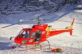 stock photo of helicopter  - Red helicopter landed at swiss ski resort near Jungfrau mountain - JPG