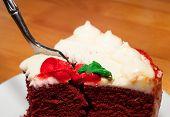 stock photo of red velvet cake  - Fork diving into a red velvet cake on a white plate - JPG