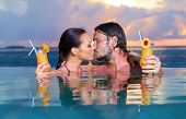 foto of hand kiss  - Romantic couple alone in infinity swimming pool - JPG