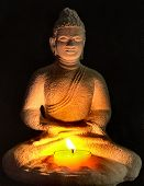 image of siddhartha  - A limestone statue of Buddha is illuminated by a candle - JPG
