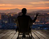 pic of city silhouette  - Silhouette of businessman sit on chair and hold a cigar and looking at the city in night - JPG