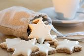 stock photo of desert christmas  - Cinnamon stars christmas cookies  falling out of a small bag - JPG