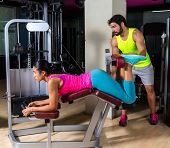picture of hamstring  - Lying hamstring curl machine girl with personal trainer man - JPG