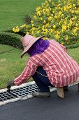 pic of manhole  - Worker in Asia painting the manhole covers  - JPG