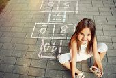 pic of hopscotch  - beautiful cheerful little girl playing hopscotch on playground outside - JPG