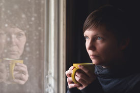 image of heartbreaking  - Lonesome woman drinking cup of coffee by the window of her living room looking out at snow falling with a sad look on her face. 