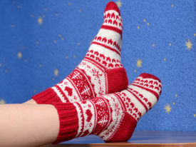 picture of stocking-foot  - feet with christmas socks on the table at home - JPG