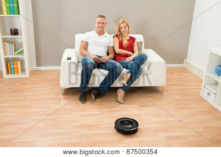 Couple With Remote Control And Robotic Vacuum Cleaner