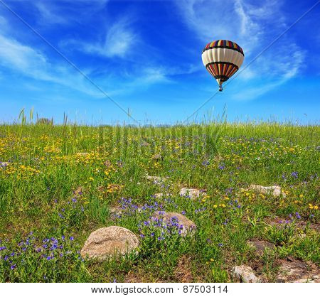 Flowering Golan Heights in a beautiful sunny day. In a clear sky flying big colorful balloon