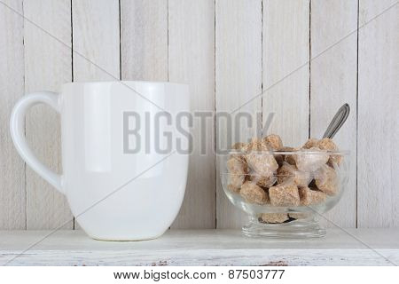 A bowl full of natural brown sugar cubes and a coffee cup on rustic white wood kitchen shelf. Horizontal format.