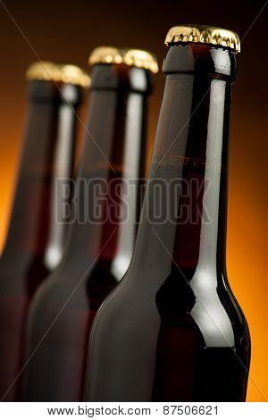 Three Brown Bottles Of Beer Standing In Row On Orange Background