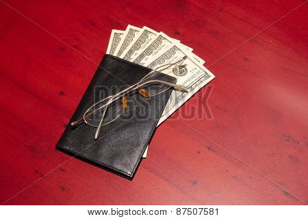 purse, old glasses and dollars