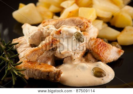 Grilled Turkey Meat With Cheese Sauce And Capers On Black Plate With Potatoe And Branch Of Rosemarry