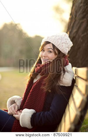 Young Girl Sitting On Bench In A Park