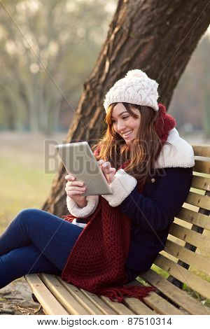Girl Sitting With Tablet On Bench In Park