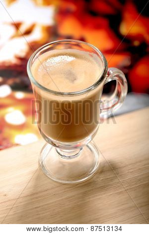 Glass of latte macchiato coffe on wooden table