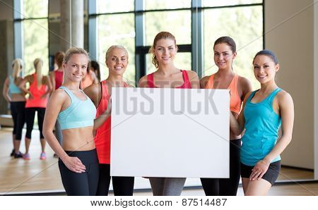 fitness, sport, training, gym and lifestyle concept - group of women witn white blank billboard in gym